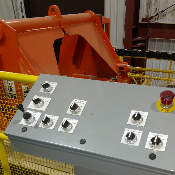 Industrial controls button station with machine in background